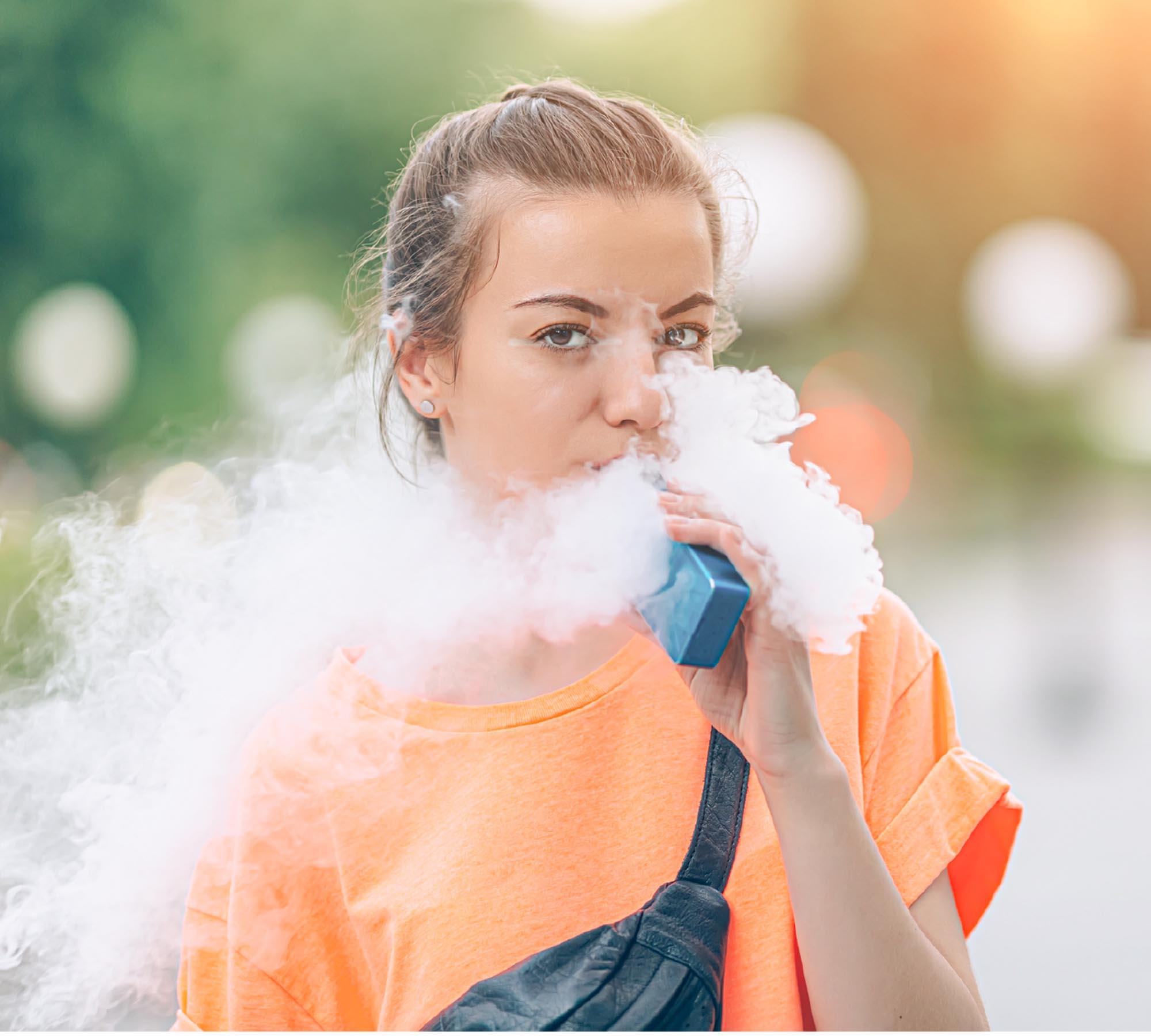 Mujer vestida de anaranjado, soltando una nube de vapor densa